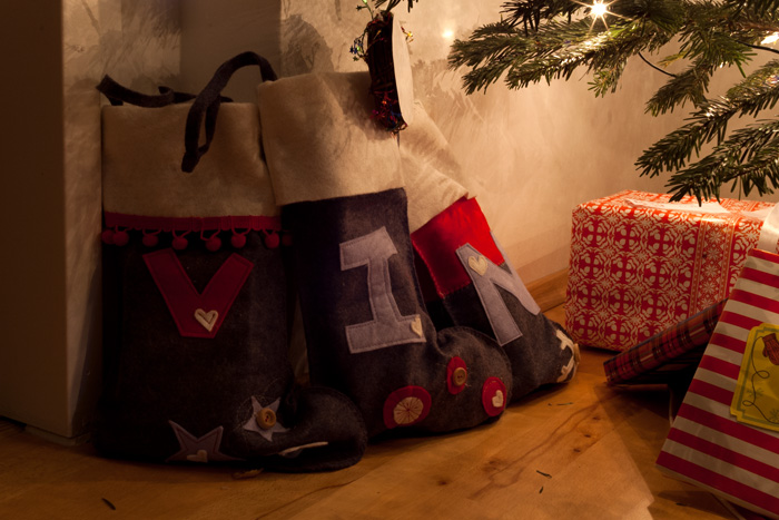 The stockings all lined up on the floor below the tree with care